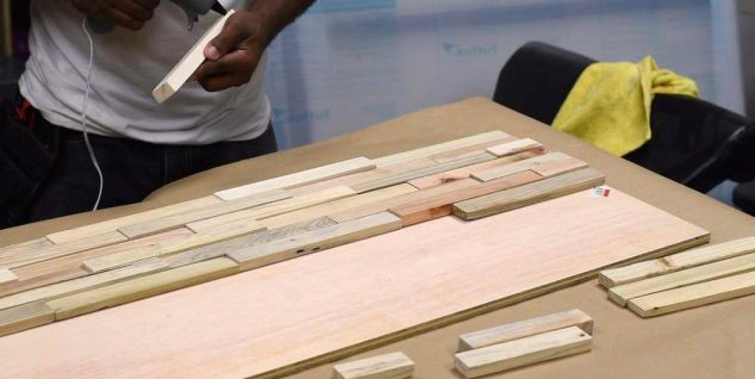 He sticks pieces of wood he got from an old palette: his idea is amazing!