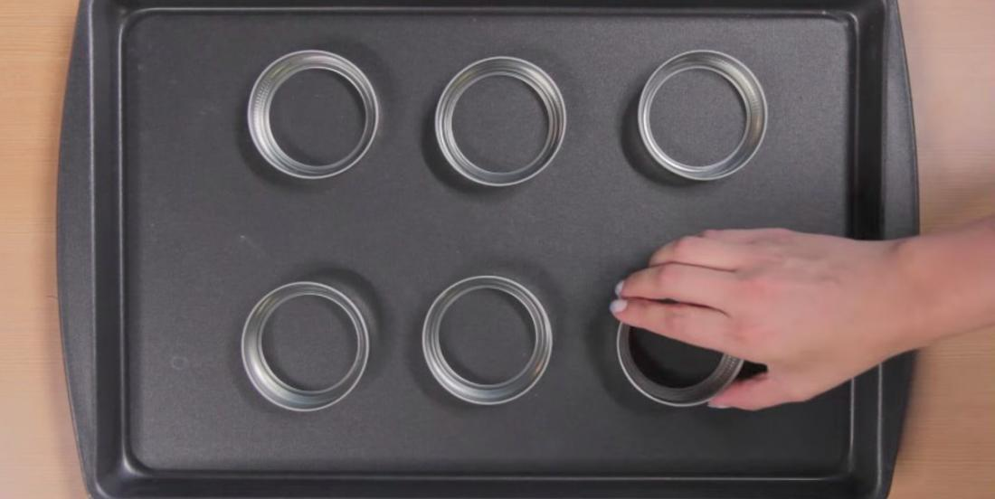 She places Mason jar lids on a baking tray! What a bright idea!