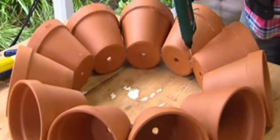 He puts 11 flower pots in a circle on a table and glue them together. When he's done the result is absolutely spectaculars